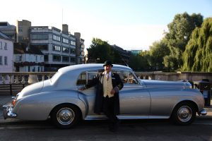 Elliot standing by a Gonville Hotel Bentley car