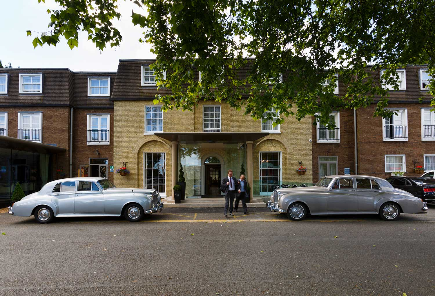 Front of Gonville hotel with two Bentley cars parked outside