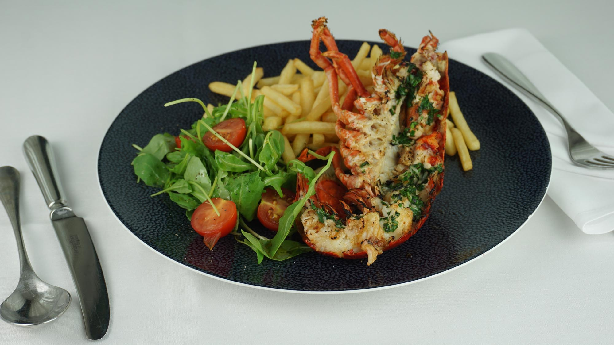Half a grilled lobster with garlic butter, salad and fries